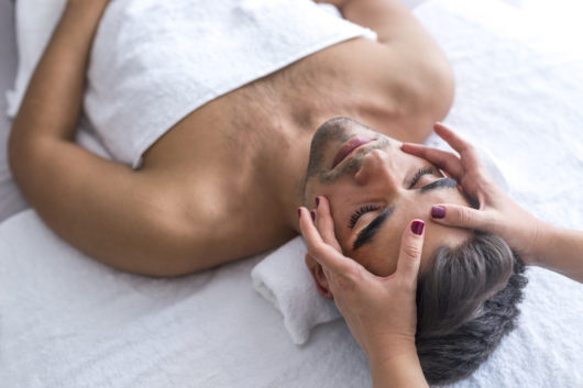 Male beauty - man receiving facial massage at luxury spa. Handsome guy, face massage. Hands of a masseuse working. Handsome man at the spa getting a facial