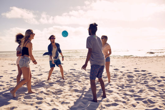 Portrait of group of happy friends having fun on the beach and playing with ball on a summer day.
