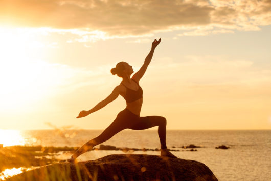 caucasian fitness woman practicing yoga at sunset