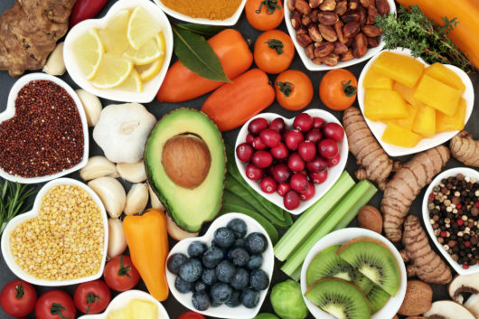 Health food for fitness concept with fresh fruit, vegetables, pulses, herbs, spices, nuts, grains and pulses. High in anthocyanins, antioxidants,smart carbohydrates, omega 3 fatty acids, minerals and vitamins.