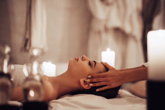 Attractive young woman is relaxing in spa and wellness center while receiving head massage. Beauty treatment concept.