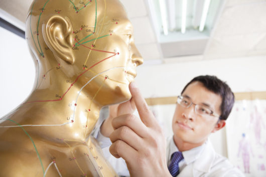 chinese medicine doctor teaching Acupoint on Human acupuncture model